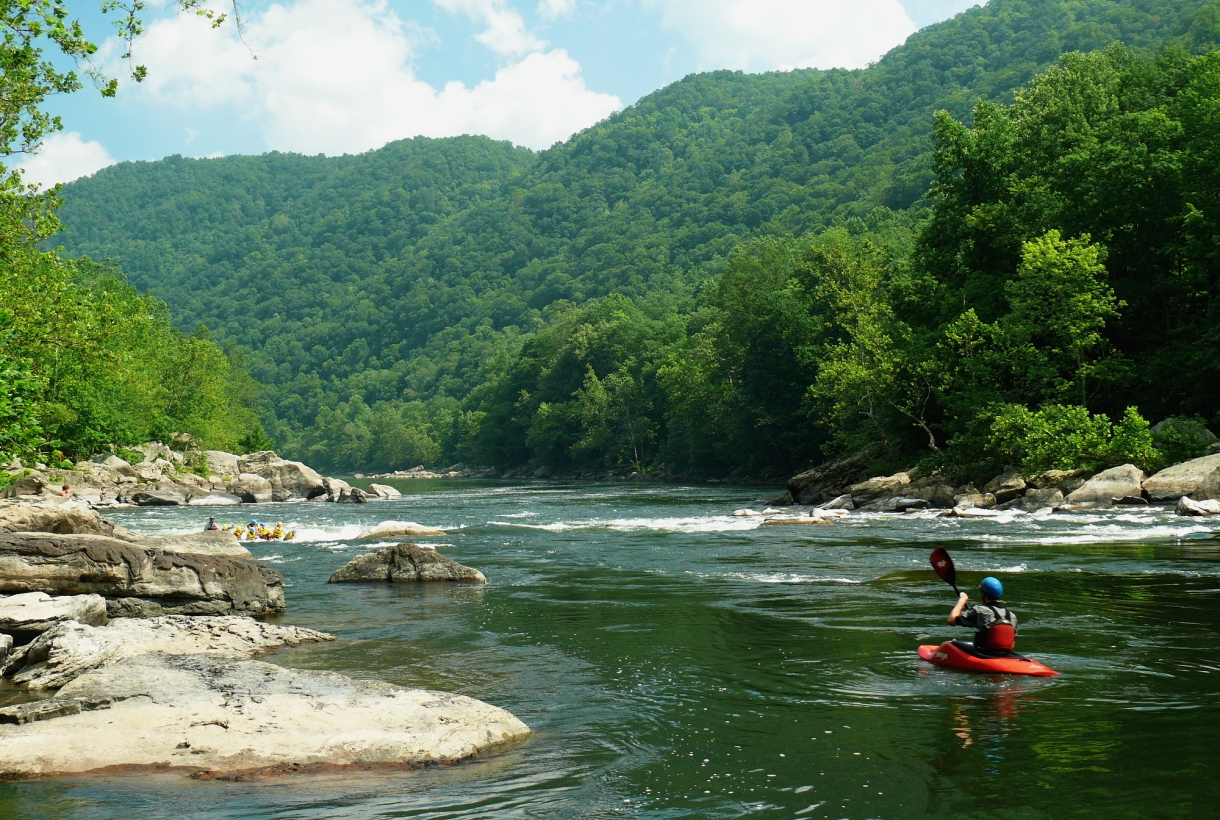 a lone kayaker paddling through new river gorge