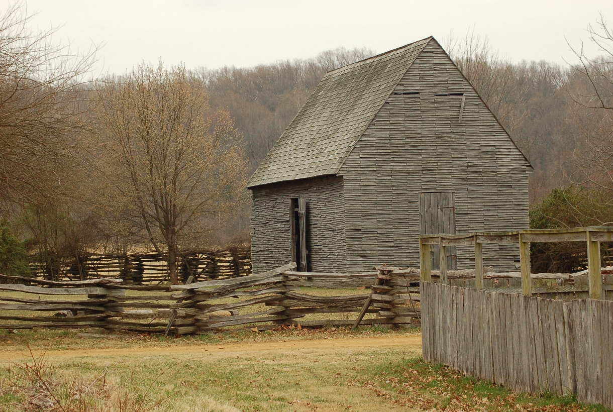 Historic cross hatch log fences and a wooden clapboard house