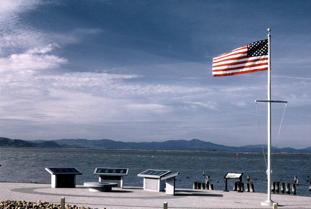 American flag waves in the wind at memorial with four plaques and water behind