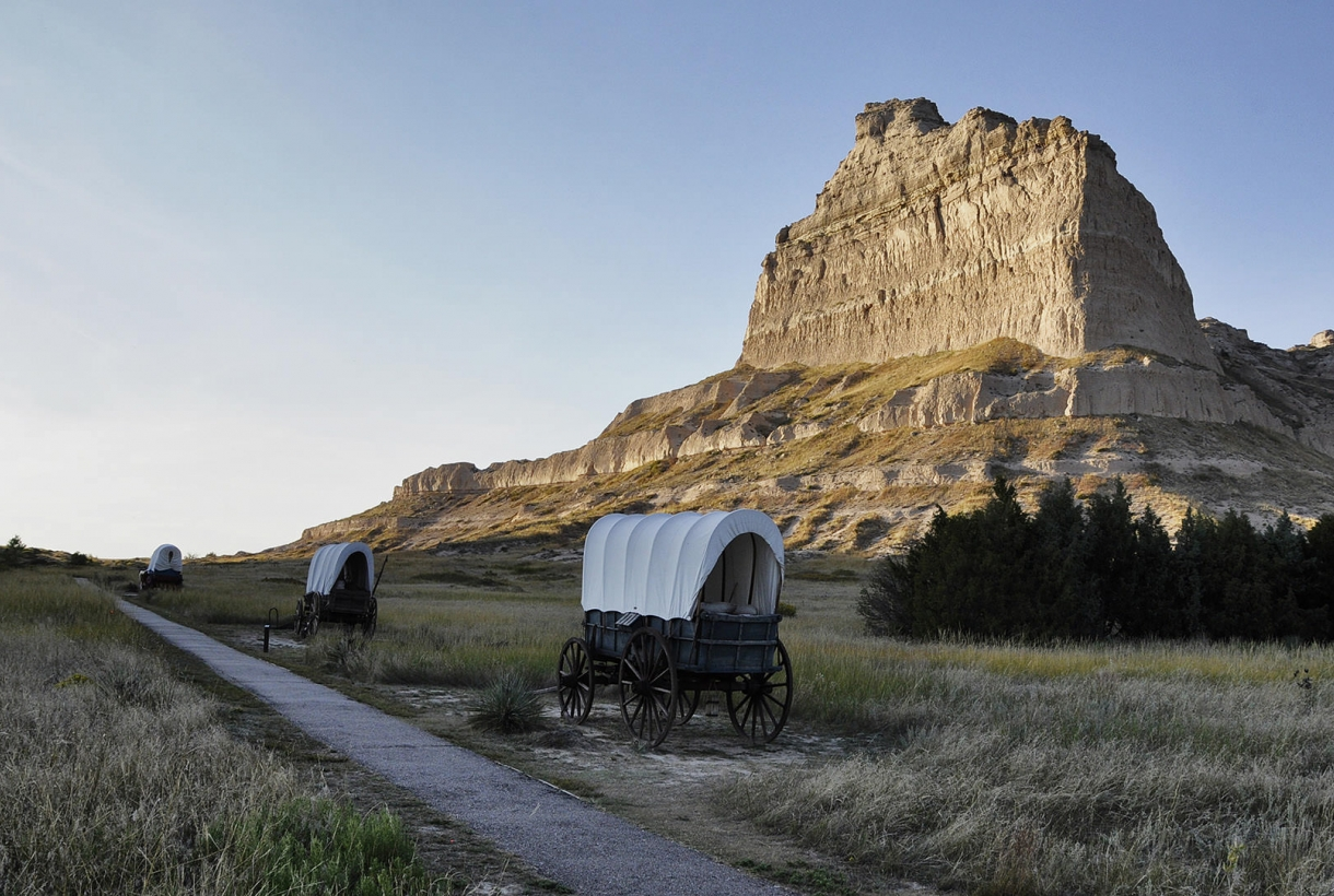 covered wagons in front of mountain