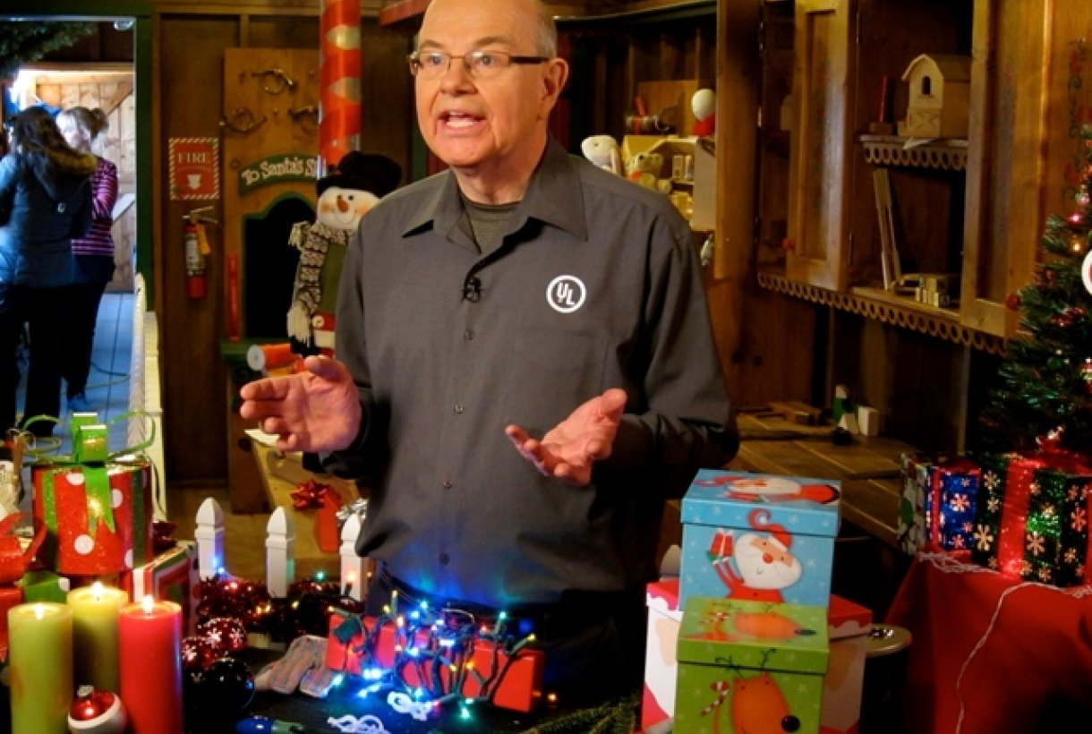 Man surrounded by holiday lights explaining fire safety