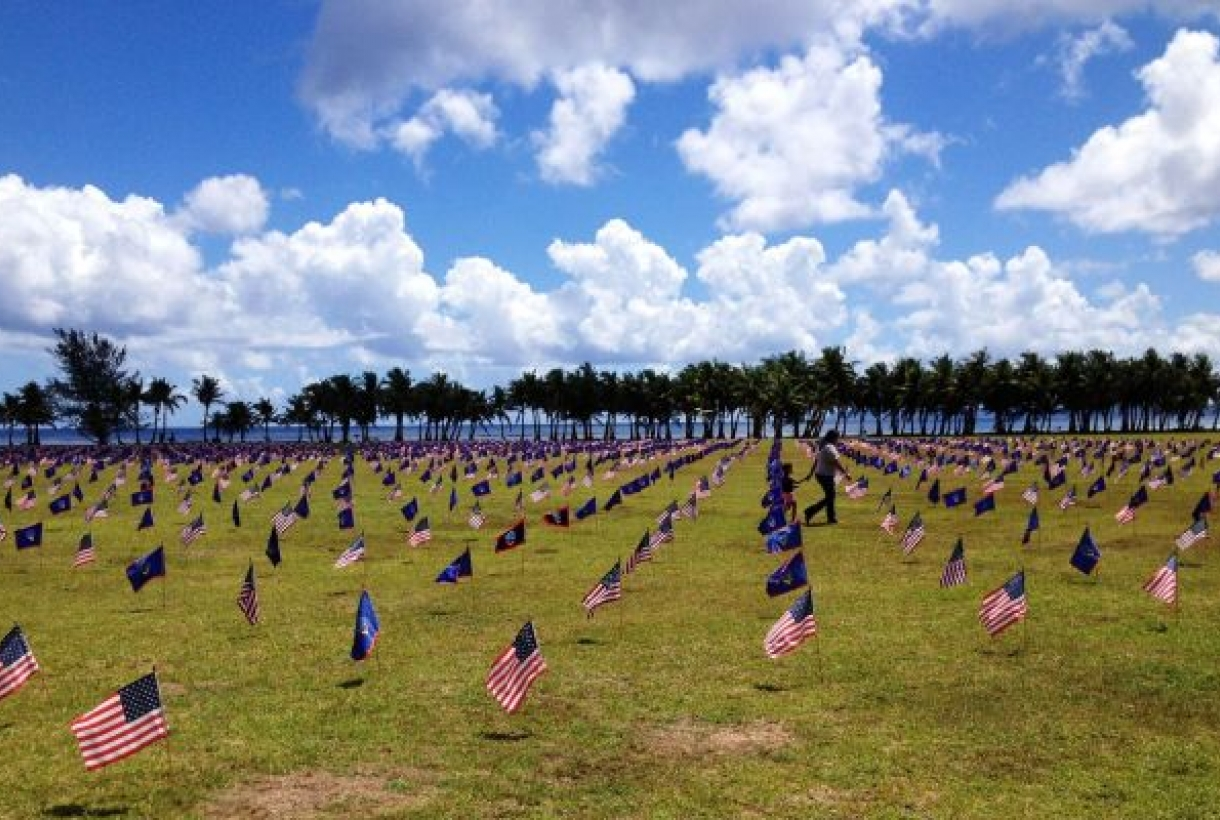 Sunny day with American flags displaying in the lawn at the War in the Pacific National Historical Park