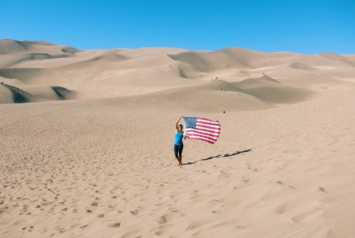 Person holding American Flag on sand dunes