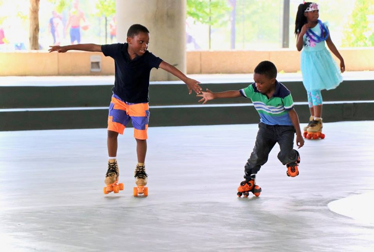 Two kids roller skate in a covered skating rink