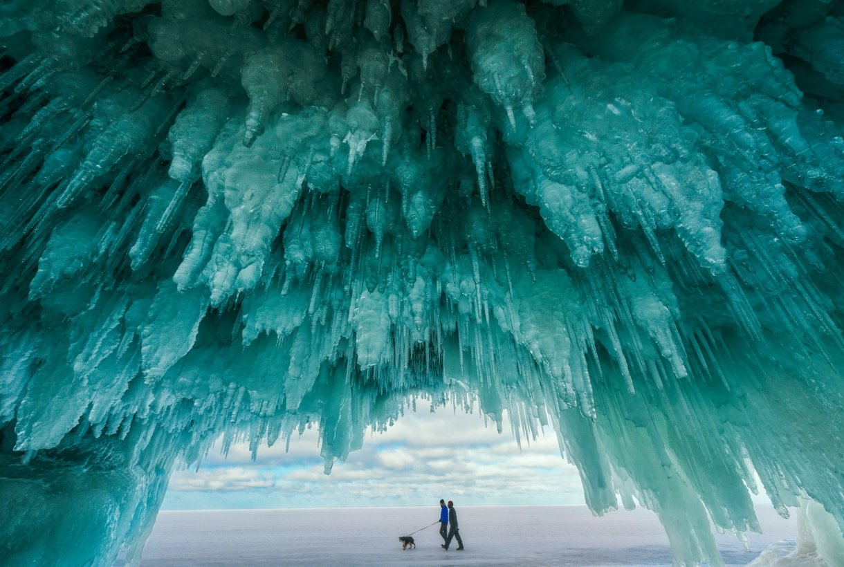 Icicles from within a cave at Apostle Islands National Lakeshore frame two people walking a dog over the frozen water of Lake Superior.