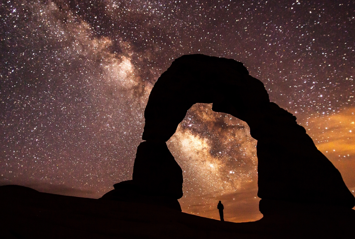the milky way and a starry sky above a silhouetted stone arch and a person standing beneath it