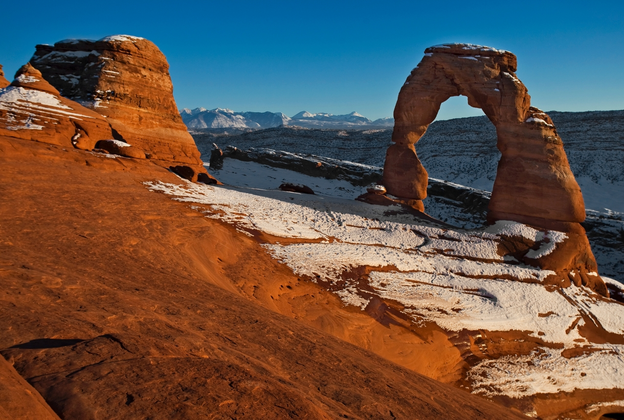Snow dusts the ground and top of the orange stone arches in Arches National Park