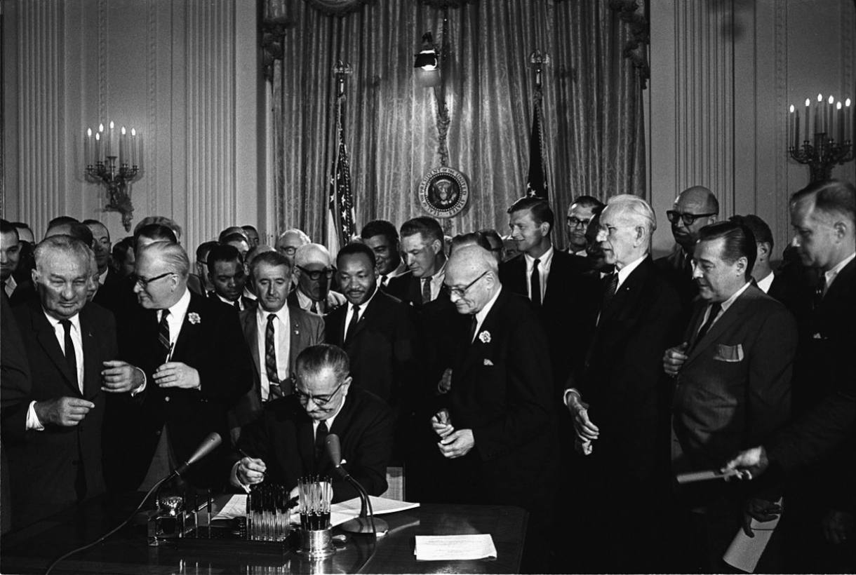 Black and white image of Lyndon B. Johnson signing the Civil Rights Acts, surrounded by many men in the White House