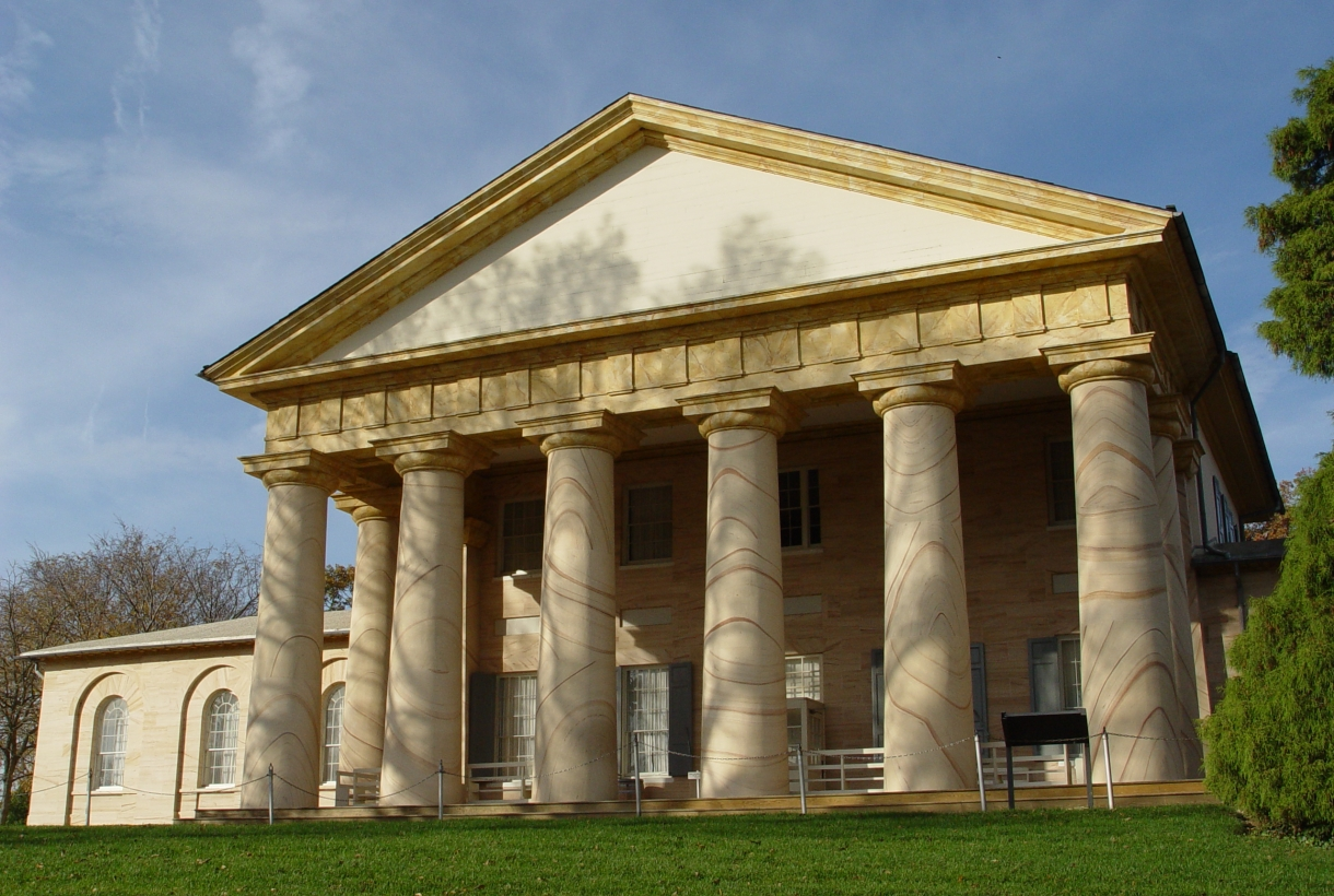 Neoclassical facade of a building, with a triangular roof and columns