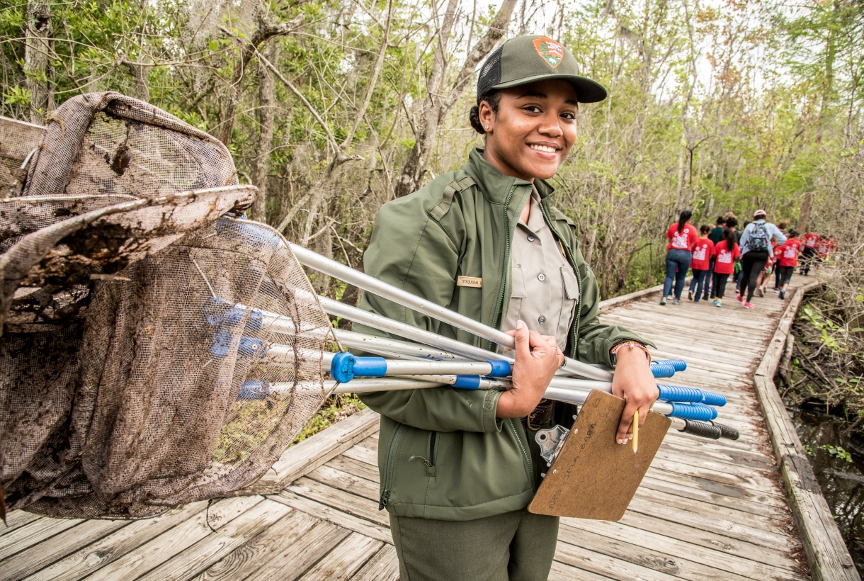 NPS employee stands with a bundle of nets, a youth group ahead of her on an elevated wooden path