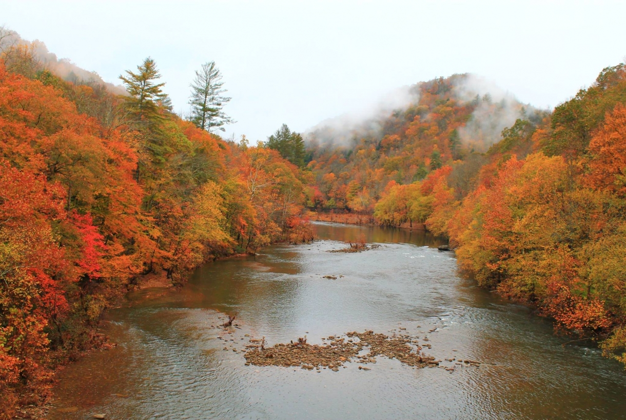 The red, orange, yellow, and green fall foliage surrounding the river
