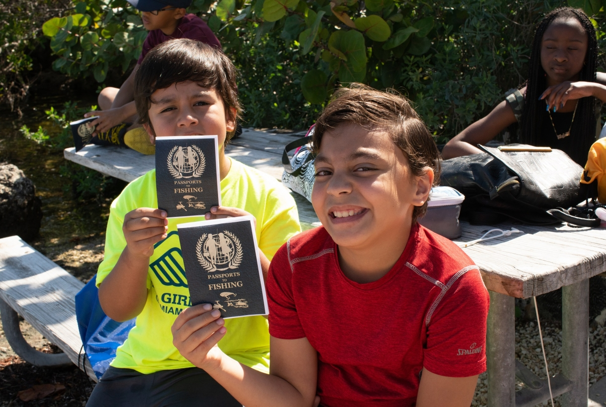 Tow kids holding fishing passport at Biscayne National Park.