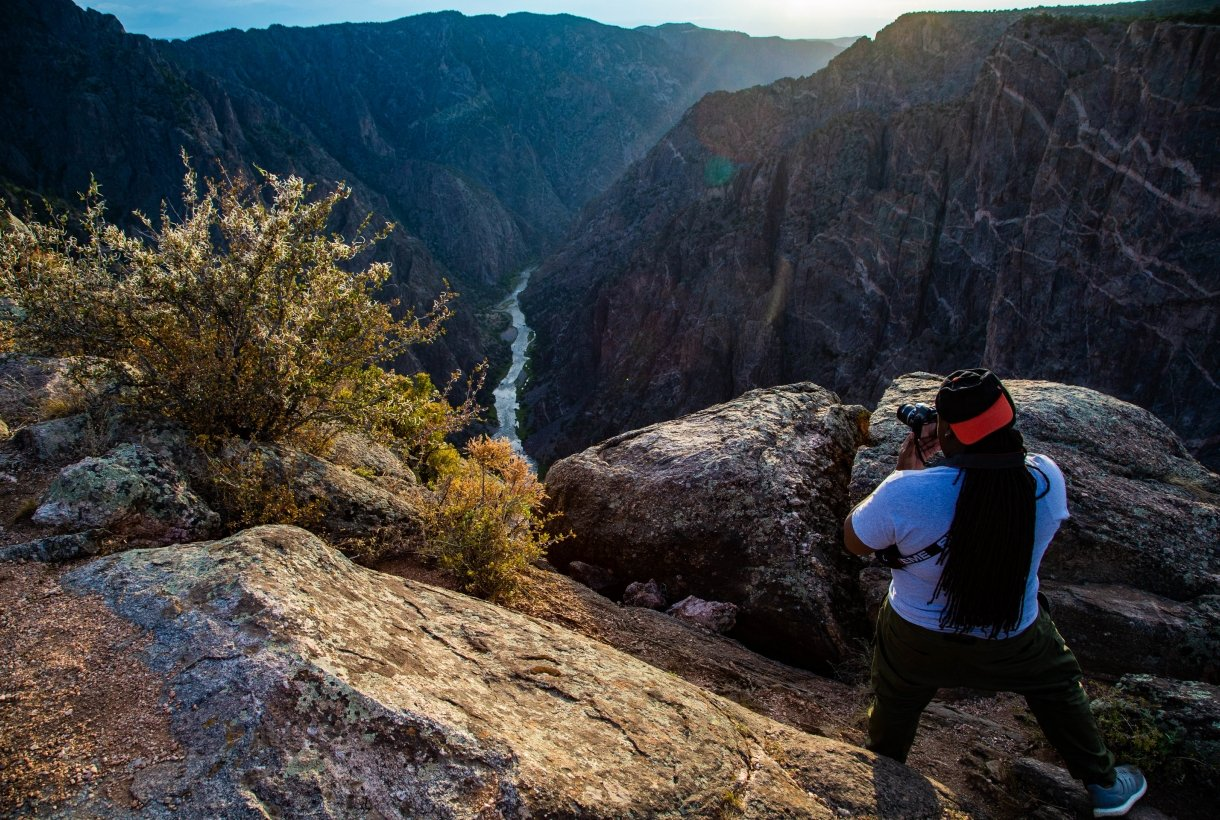 Photographer taking a picture of a river canyon at sunset