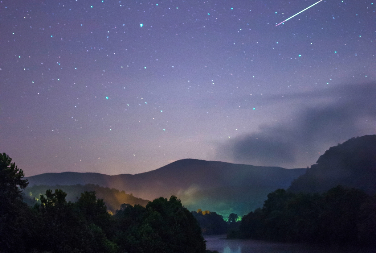 A shooting star dances downward across a starry sky, down towards a clear lake surrounded by trees