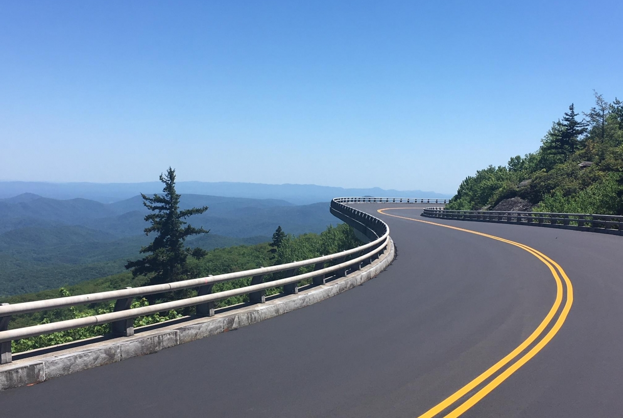 A paved winding road on a clear blue day along the Blue Ridge Parkway