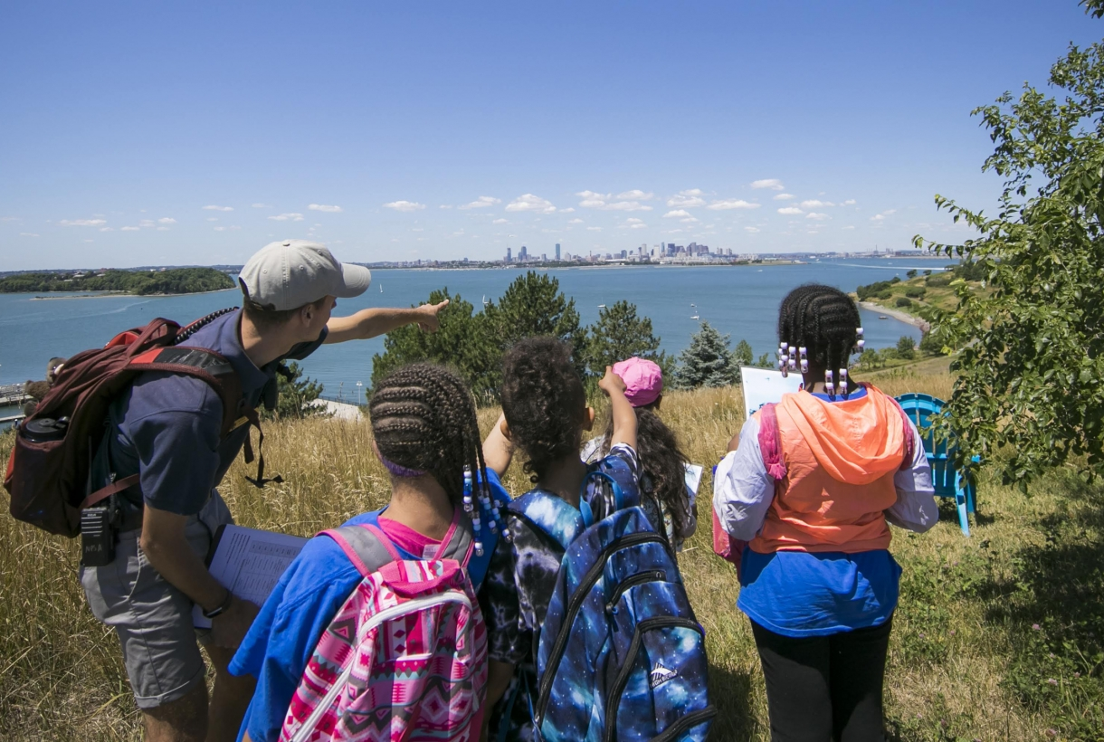 Group of young people standing outside pointing at something, looking out over water with a city sky