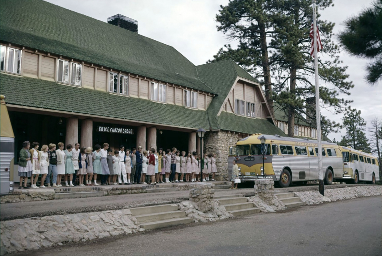 Vintage photo of a line of employees at Bryce Canyon Lodge look at a couple of buses