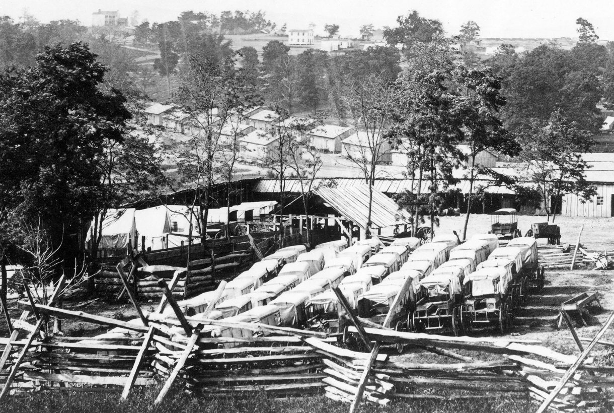 Historic black and white image of vehicles and barracks at Camp Nelson National Monument