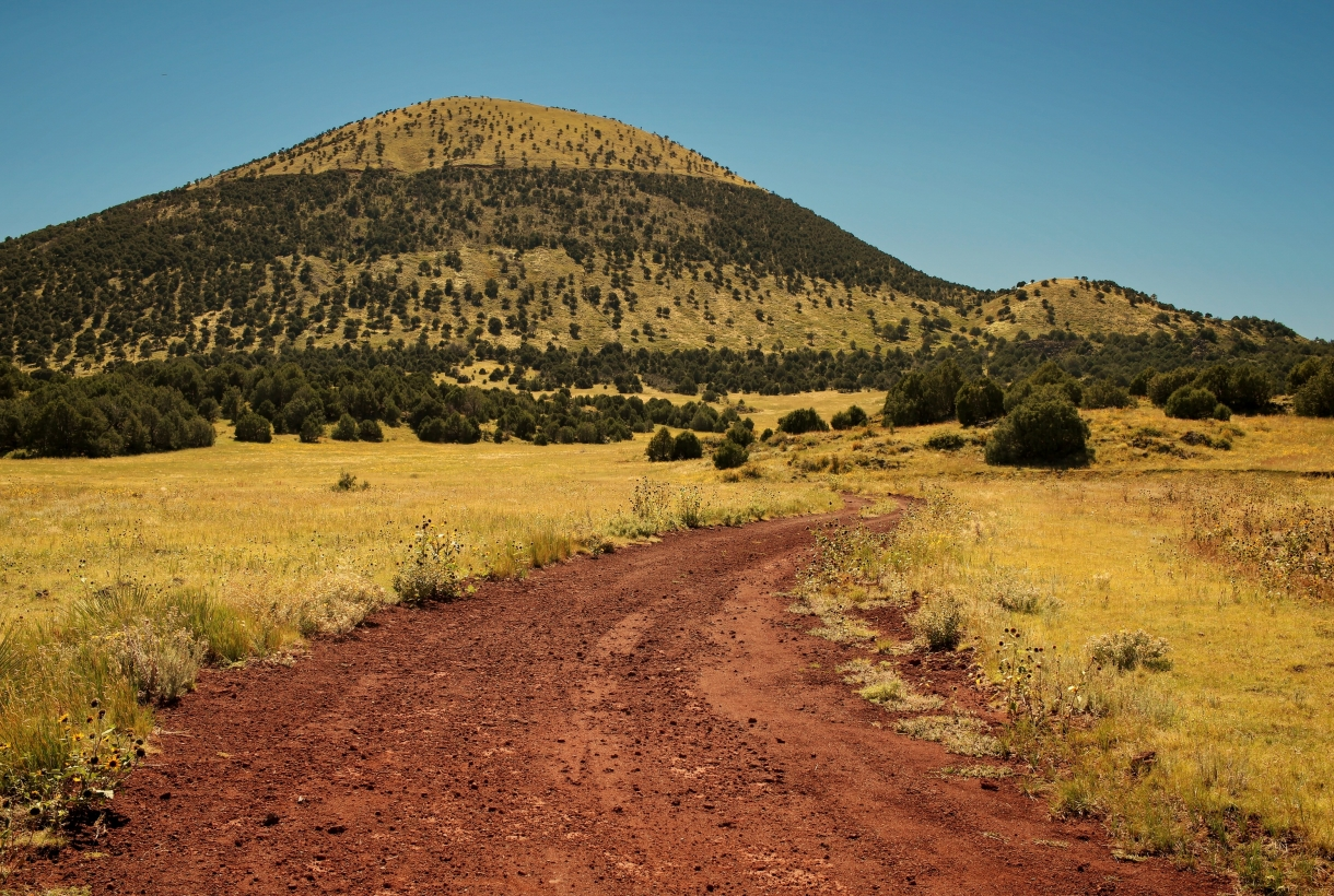 Yellow grass and green shrubbery with a red dirt path leading up to the short mountain that is Capulin Volcano National Monument