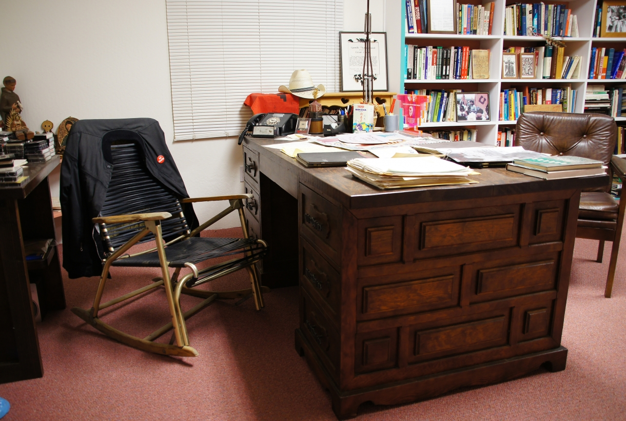 A simple chair with leather straps next to a desk and bookshelves