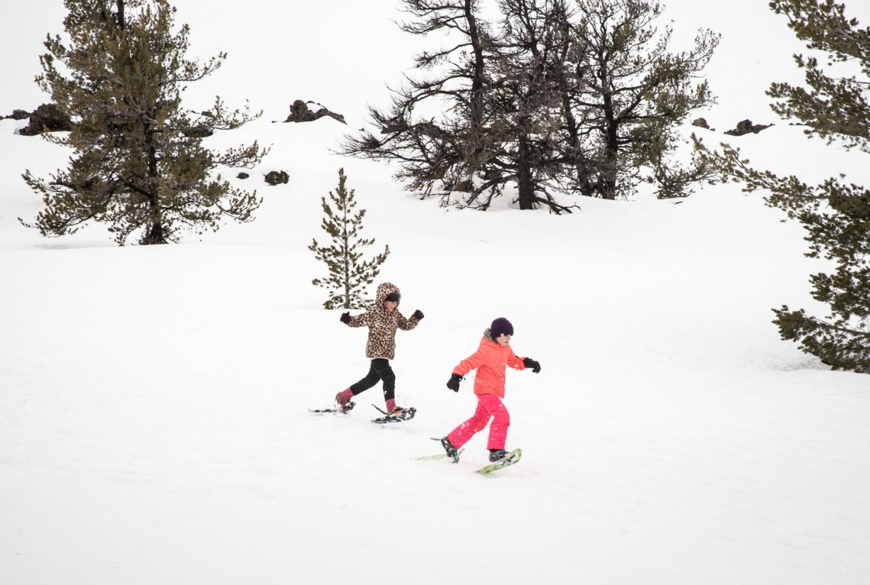 Two kids on snowshoes in the snow at Craters of the Moon National Park and Preserve