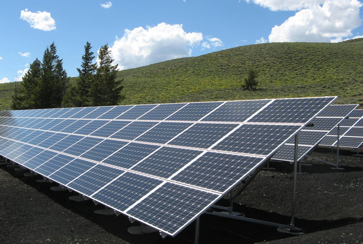 Several large solar panels mounted in front of grassy hill and some conifer trees