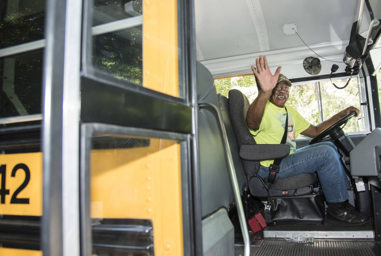 Bus driver participating in a Ticket to Ride program waves to the camera