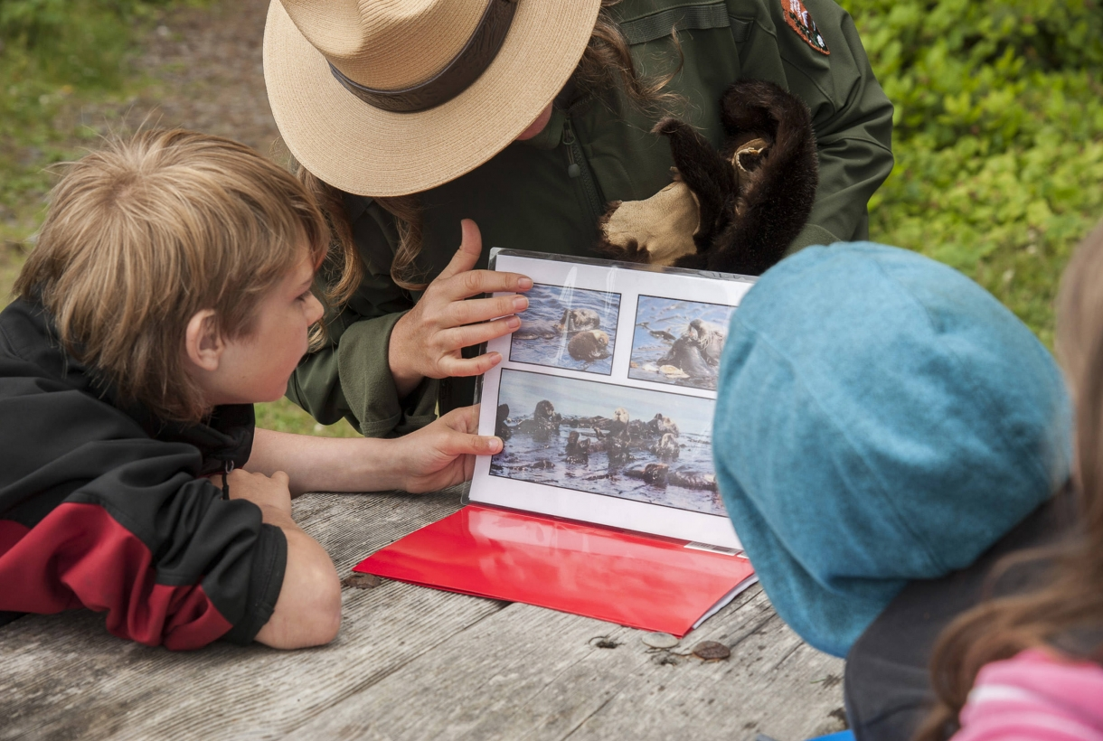 Park ranger talking about sea otters with a group of kids