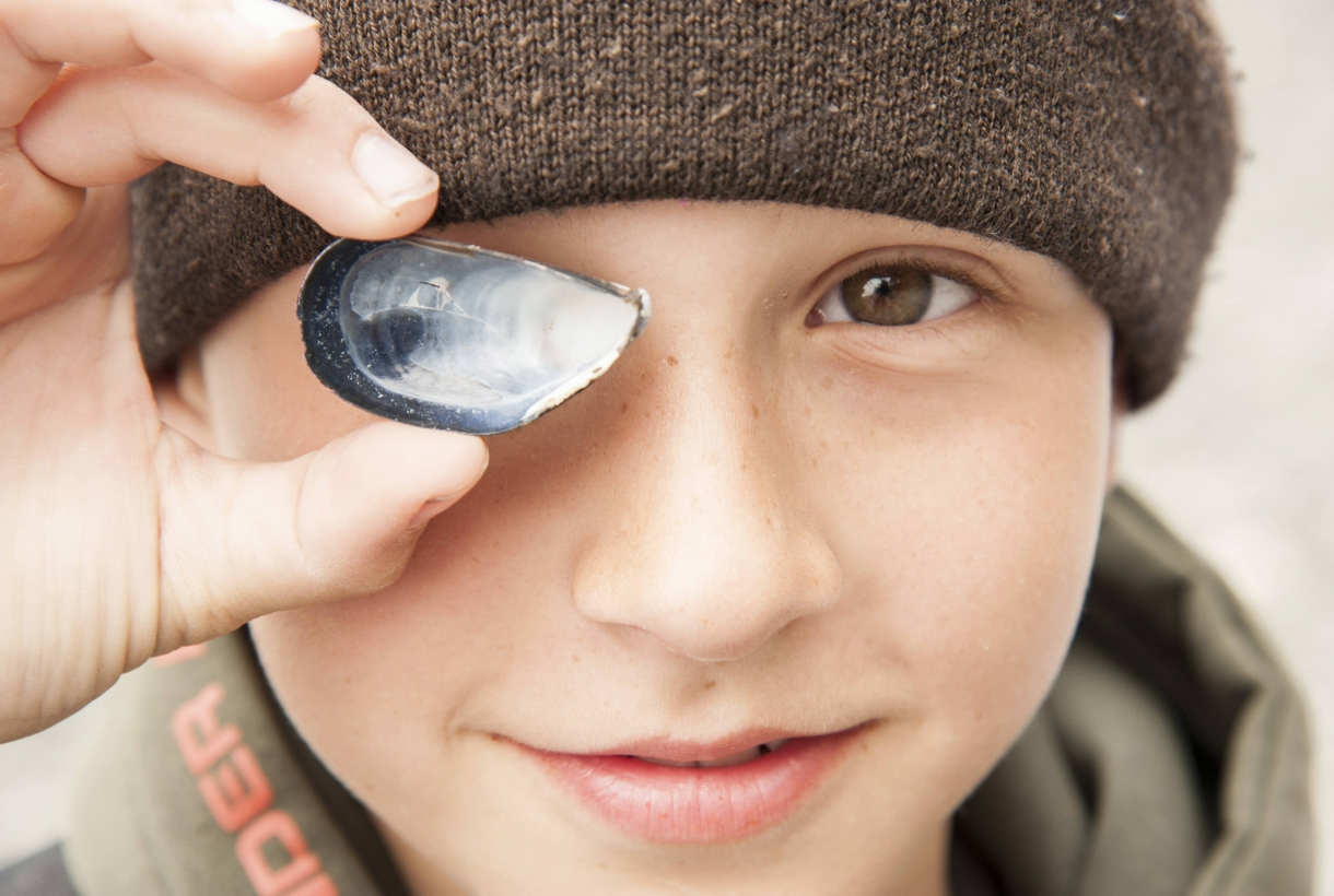 Boy at National Park river preserve poses with seashell
