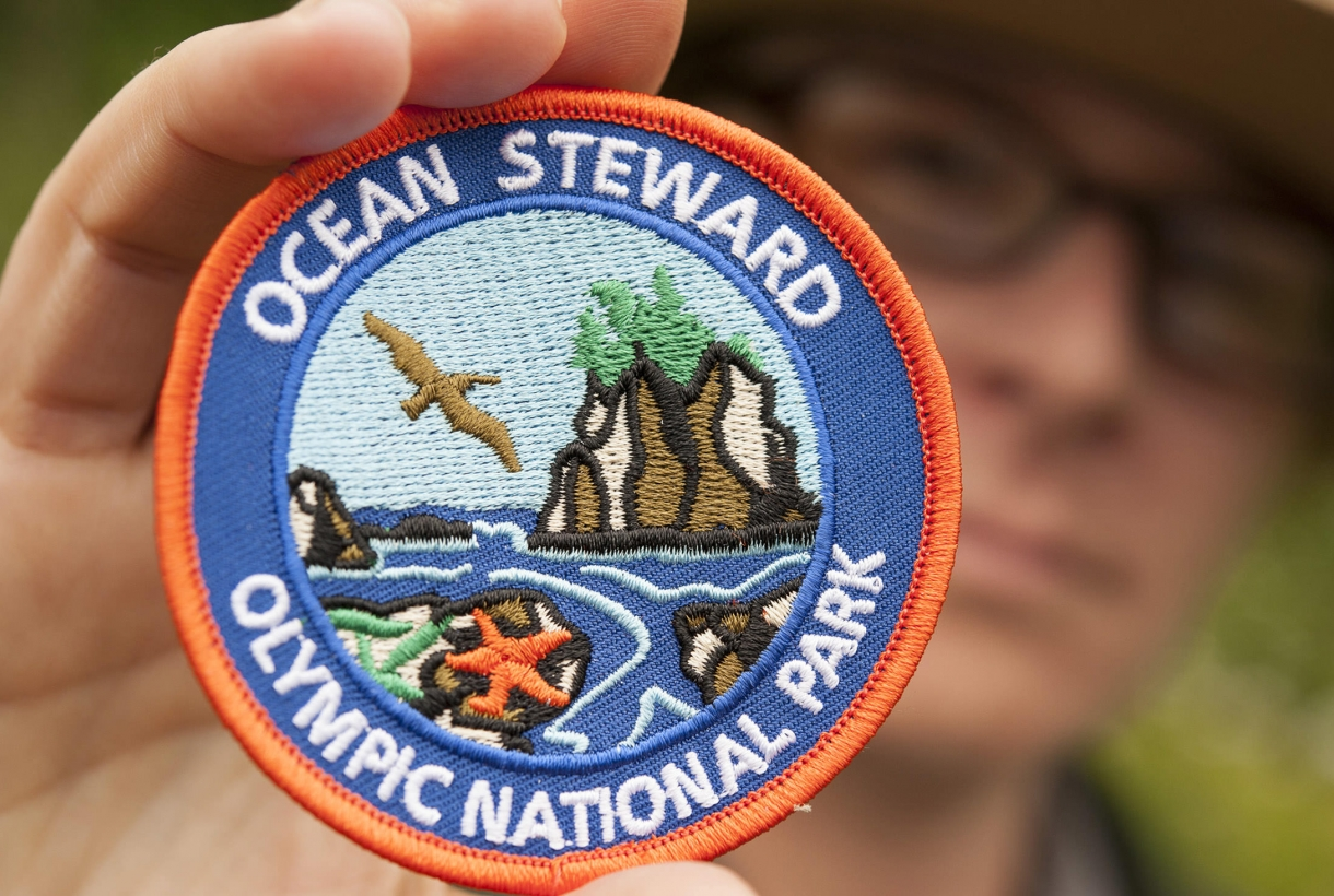 Person holding up Olympic National Park Ocean Steward patch