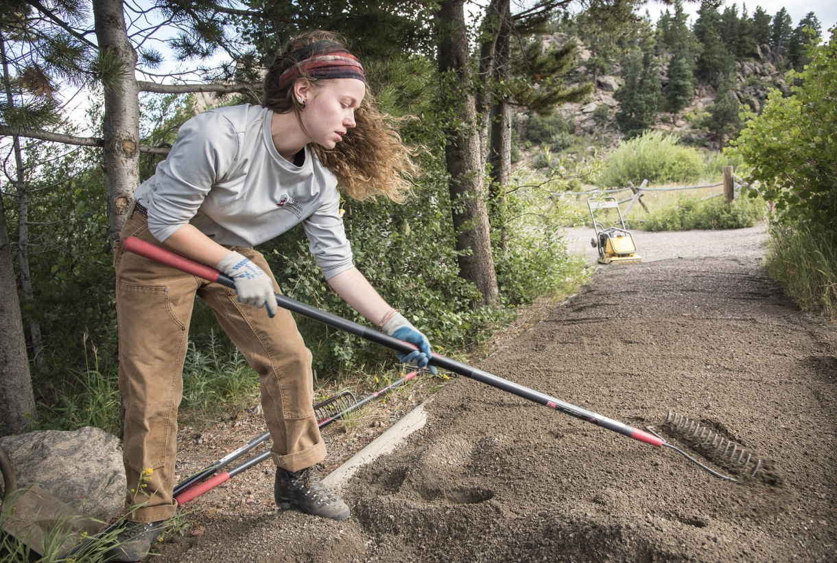 A woman helps restore a trail