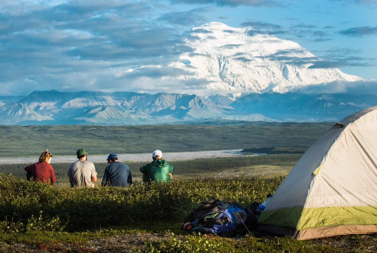 four people sitting near a tent on a hill, looking at a distant, snowy mountain