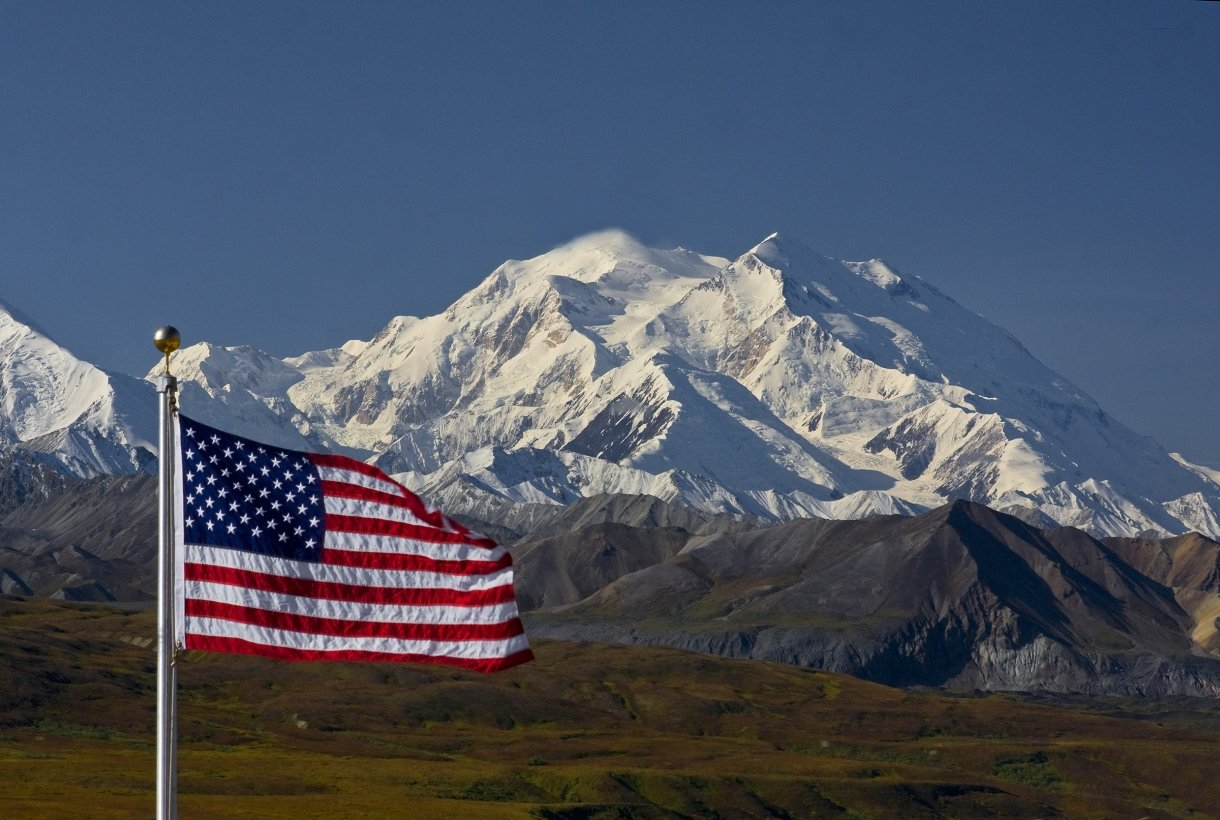 american flag flying in the foreground with a huge snowy mountain in the distance