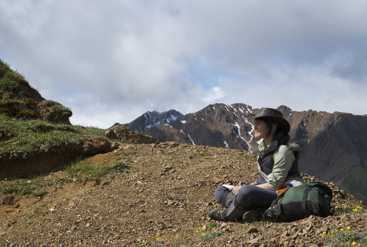 Woman seated with legs crossed on rocky ridgeline sketches view at a distance