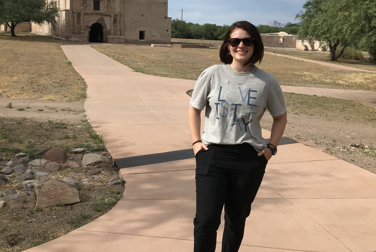 NPS Intern Dorien Scheets poses out front out Tumacácori National Historical Park