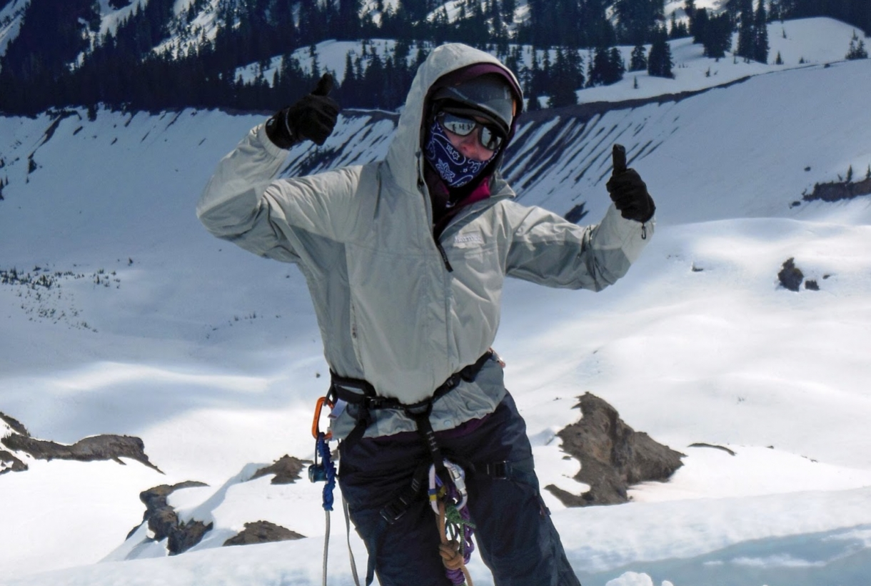 Woman dressed in mountaineering clothes wearing a harness and a helmet standing on the snow giving two thumbs up