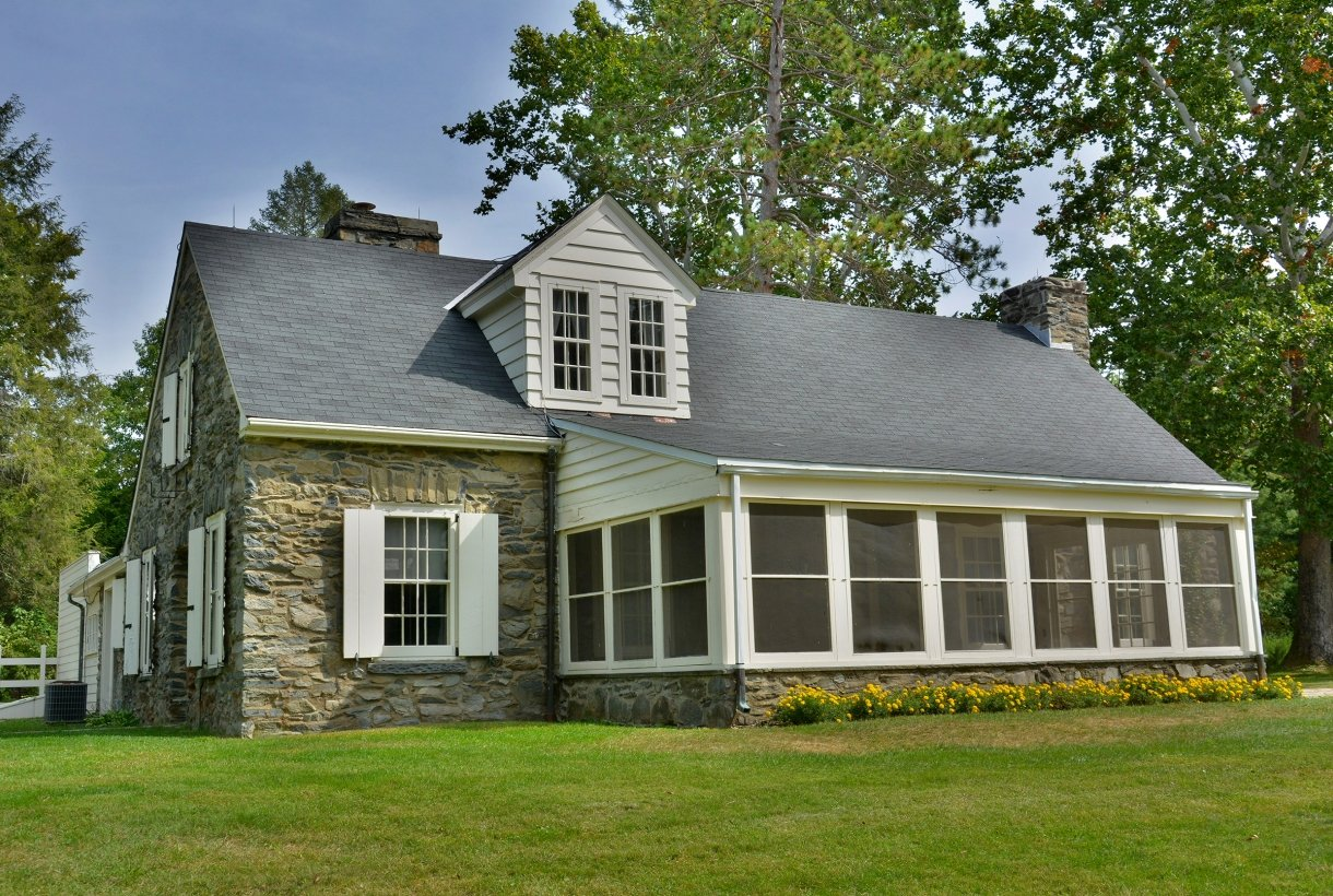A stone cottage with a screened porch and sloping roof stands on the green grounds of a landscape