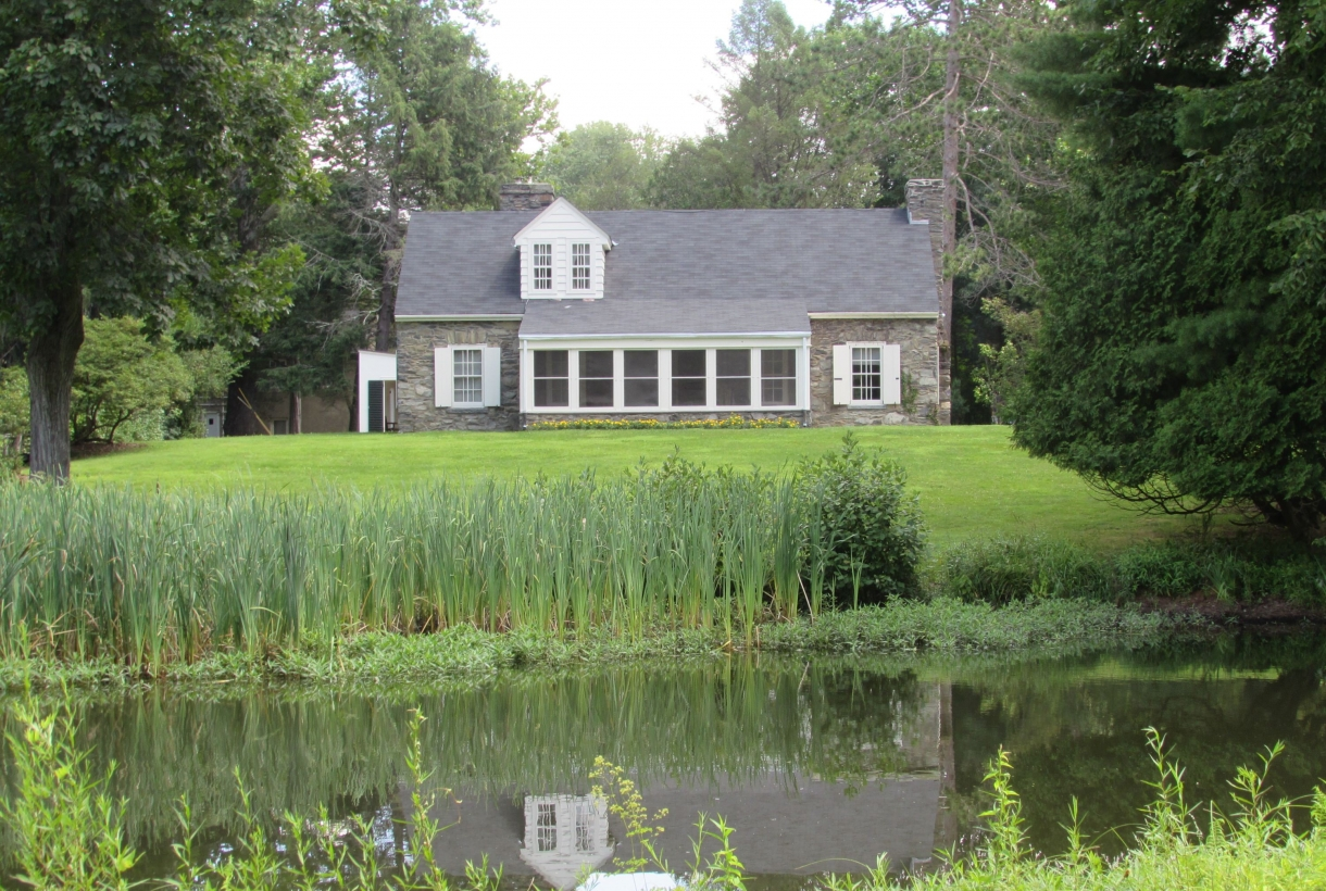 A creek surrounded by growing greenery surrounds the stone cottage, Val-Kill, at Eleanor Roosevelt National Historic Site.