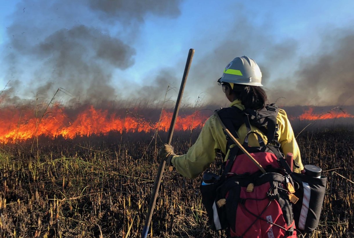 A woman in a hard hat and wearing a backpack looks out, from a safe distance, on a burning landscape
