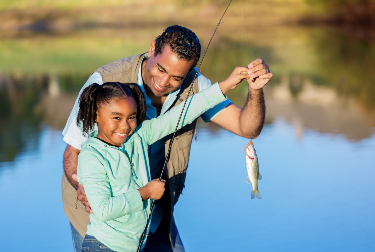 Girl smiles while showing off a fish she caught with her grandpa. They are standing on the shore of a lake or pond.