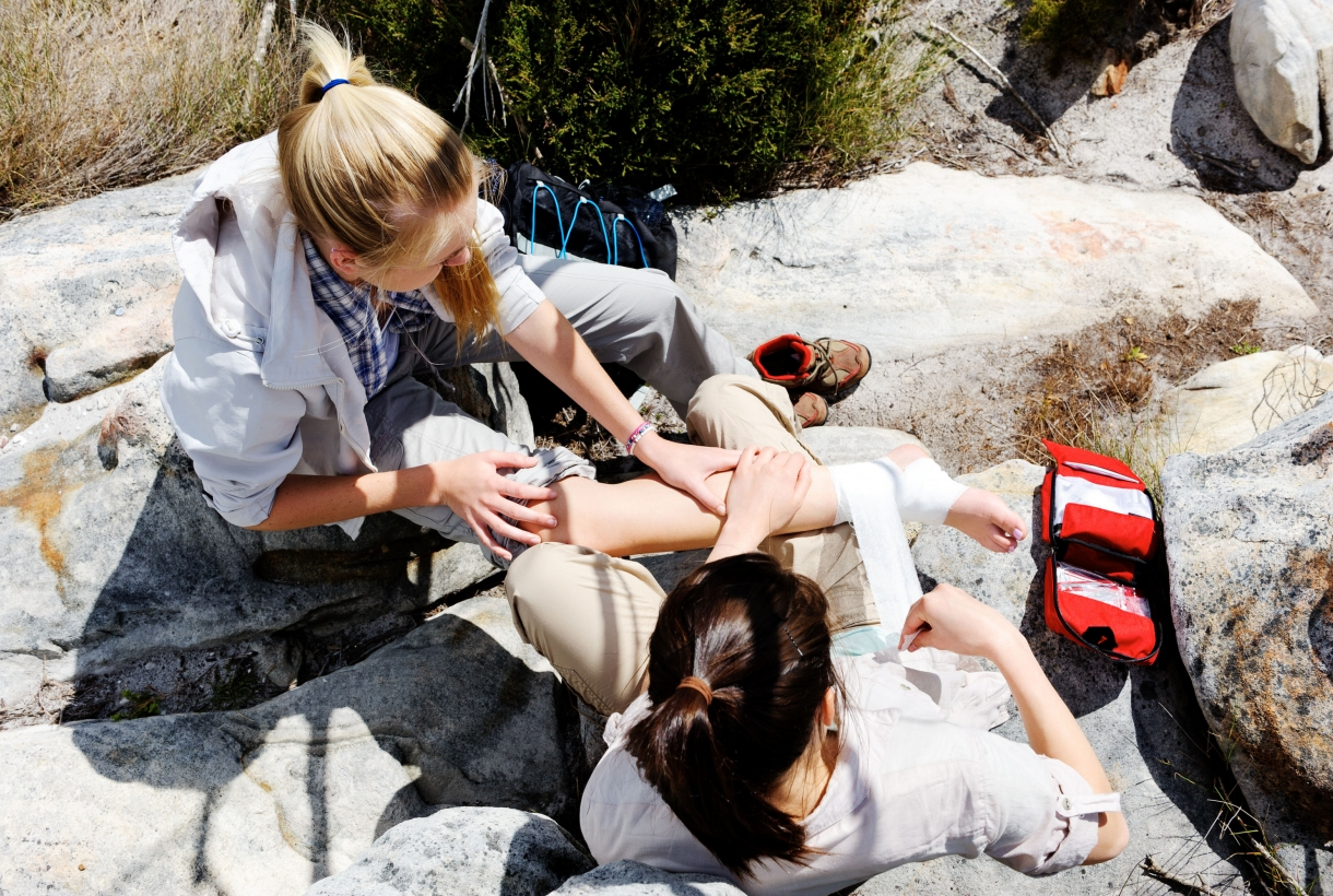 Top-down view of person wrapping the ankle of another person on the hiking trail