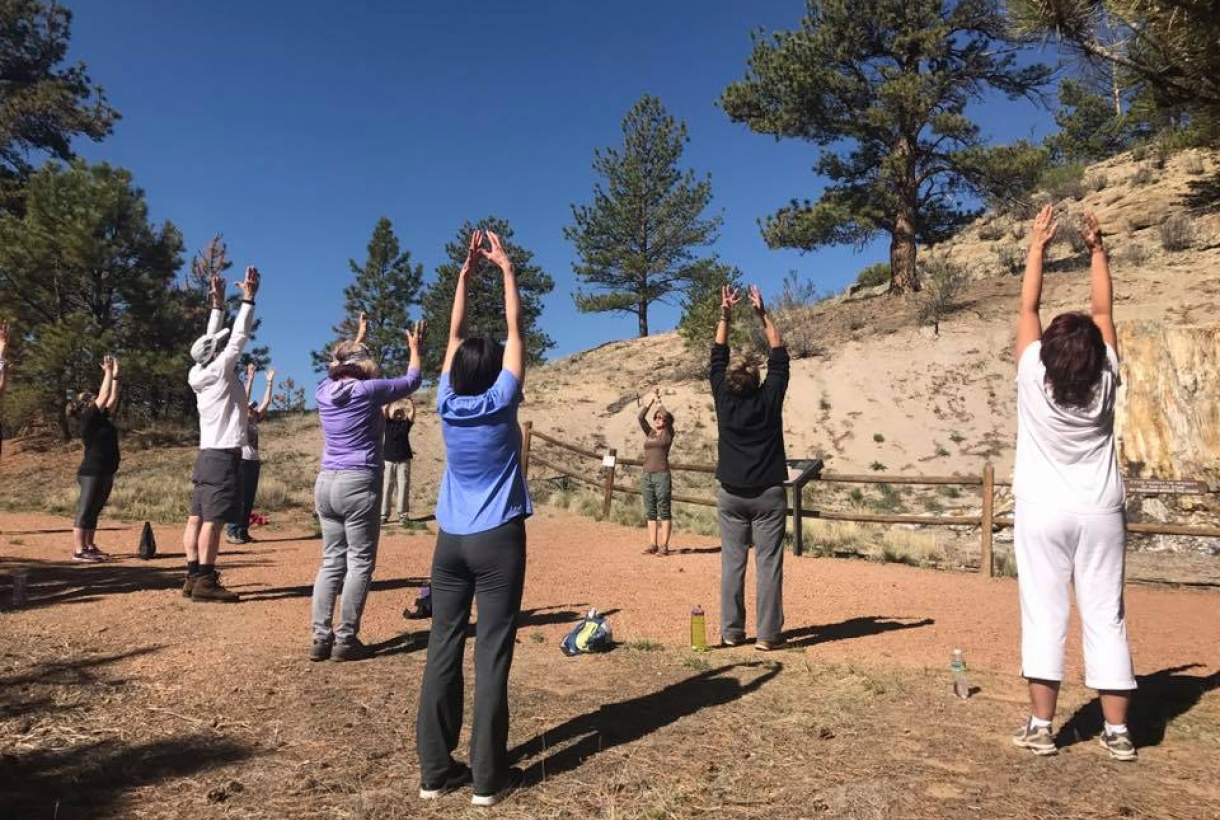 A small group of people doing a yoga sun salutation on the trails of Florissant Fossil Bed National Monument