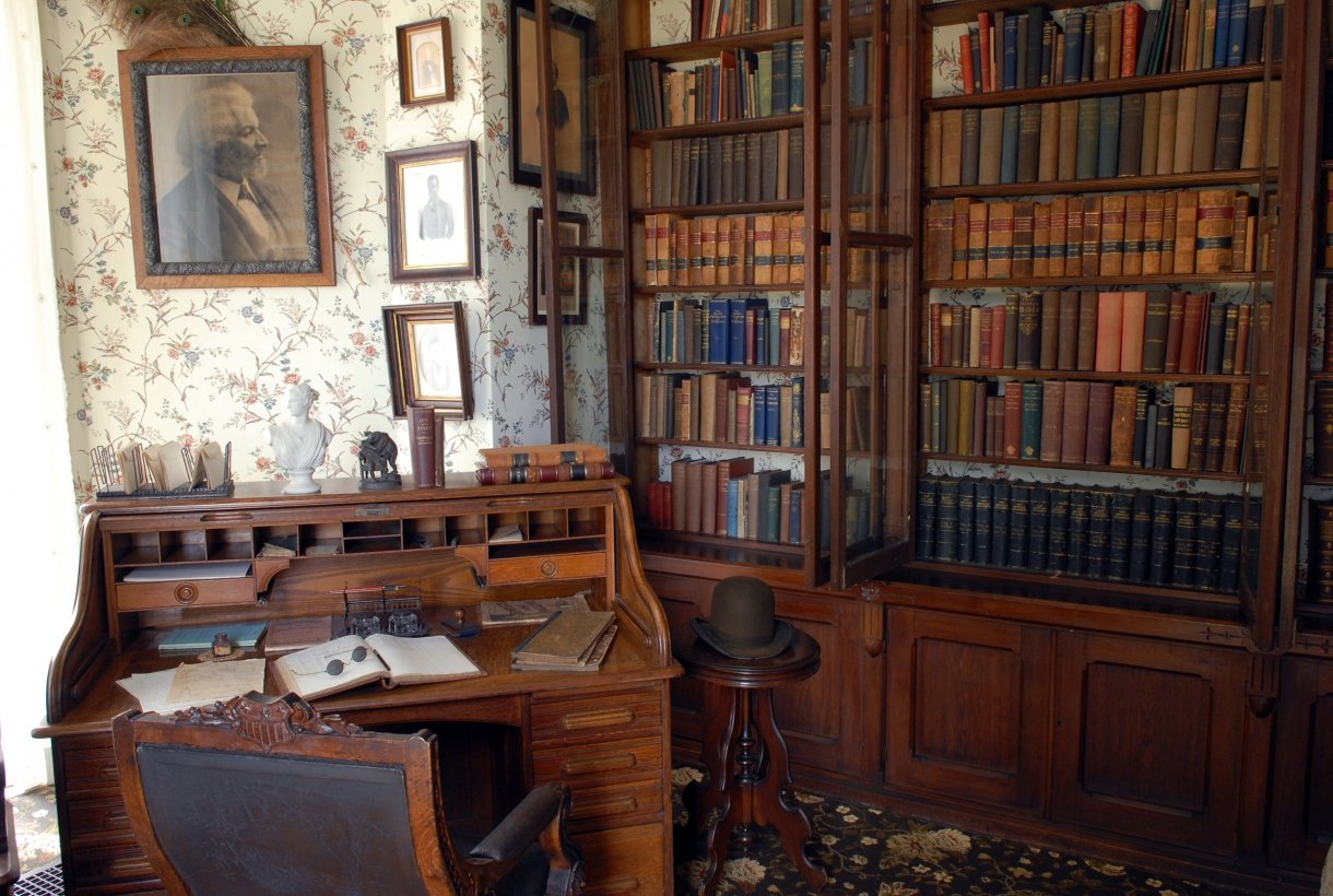 Two large bookshelves line a wall of a medium sized room. The shelves are packed with hundreds of books. A small wood desk sits in front of the book shelf. A photo of an older Frederick Douglass hangs on the wall.