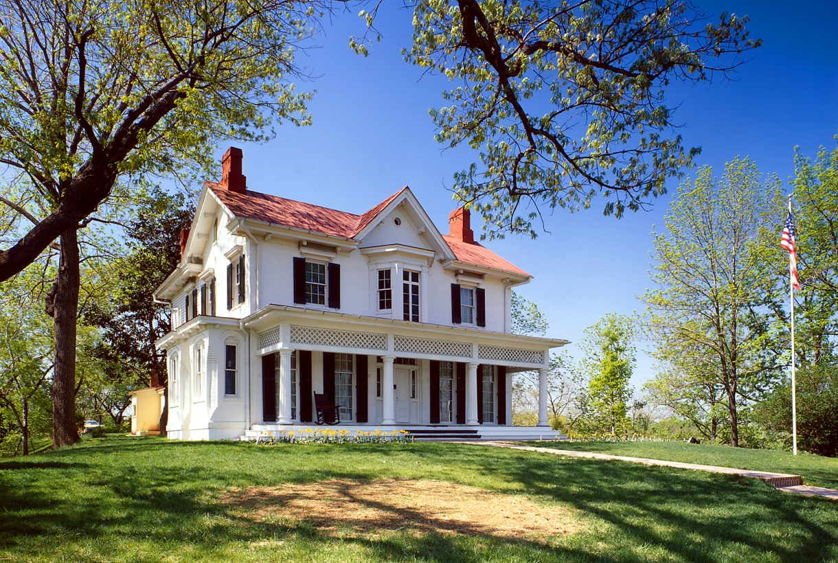 Two-story white house with black shutters, a red roof, and two brick chimneys; Cedar Hill at Frederick Douglass National Historic Site
