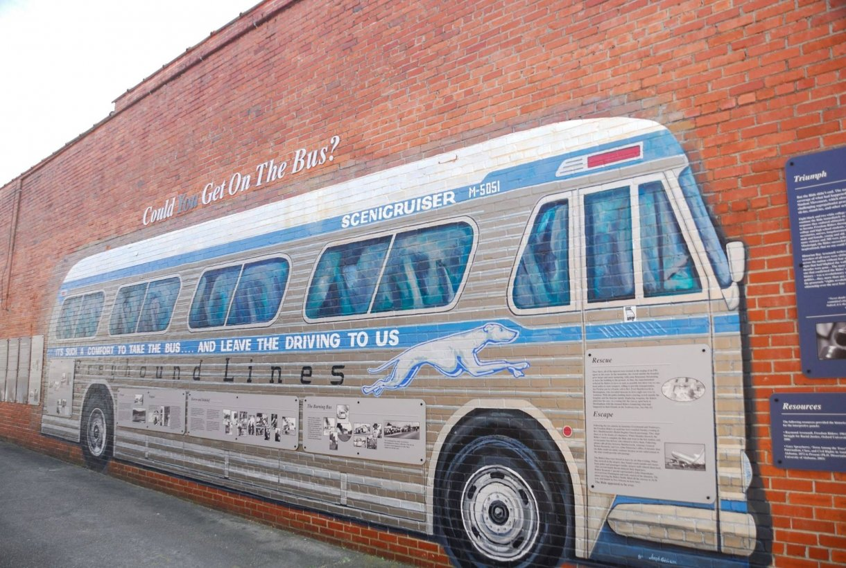 Mural of a Greyhound Bus painted on a brick wall at Freedom Riders National Monument
