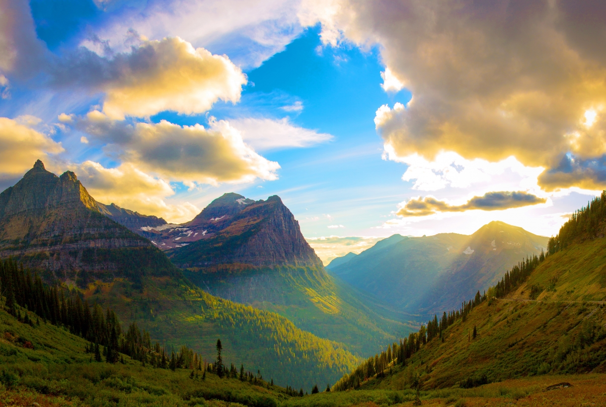 Sunrays shine through the clouds above Glacier National Park as they illuminate the green trees and grasses of the lower half of each mountain.