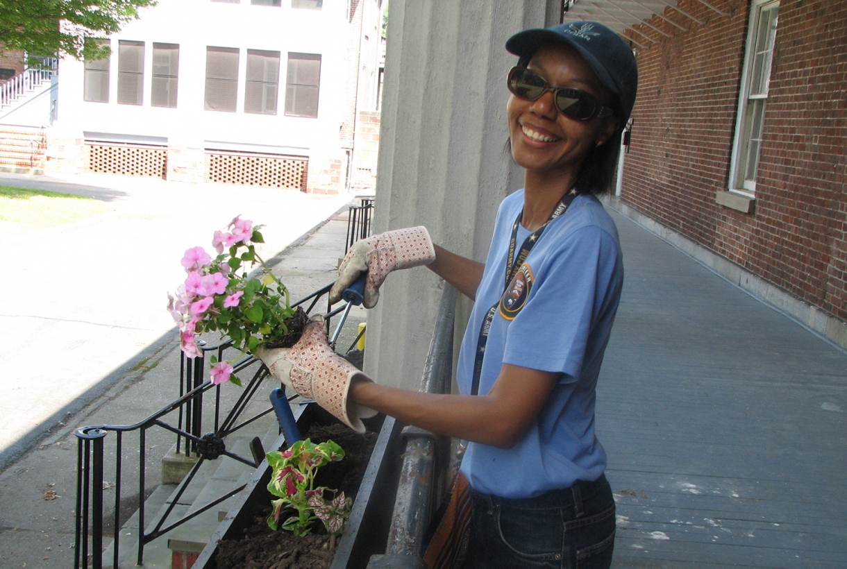 A volunteer wearing gardening gloves plants pink flowers in a flower box next to stone steps