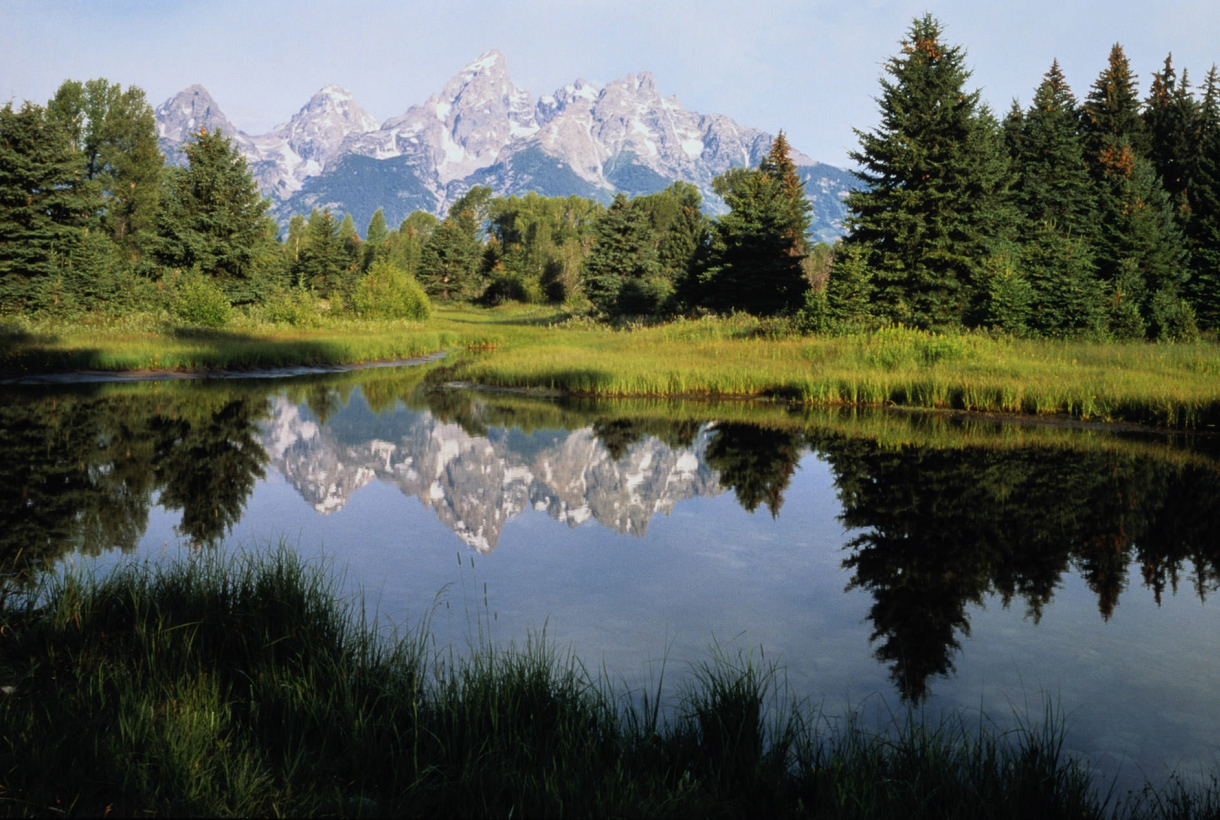 The Three Tetons are reflected in a nearby lake, creating a stunning mirror image