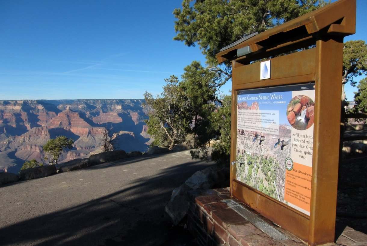 A view looking across a paved walkway into the Grand Canyon. On the right is a brown mount and colorful sign with water spigots sticking out of sign