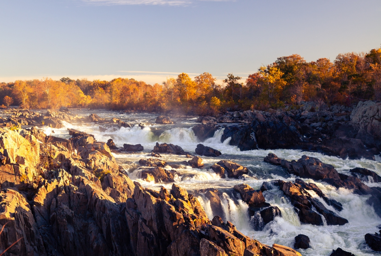 Water drops down a long waterfall. It's fall time in the morning at Great Falls Park